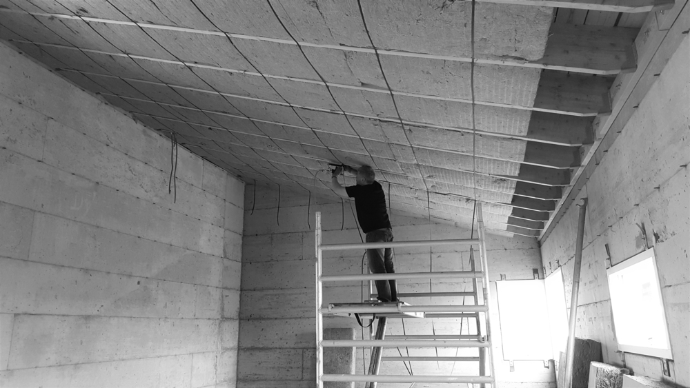 Man puting insulation on the inside of the roof