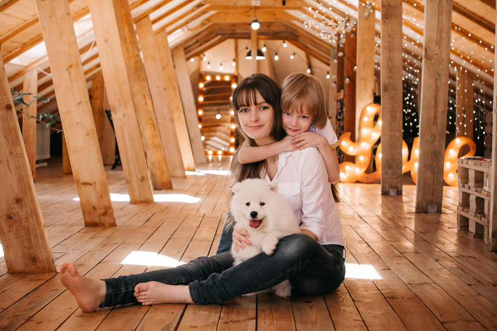 Young dark-haired mum with her son play with a Samoyed puppy in a wooden attic at home
