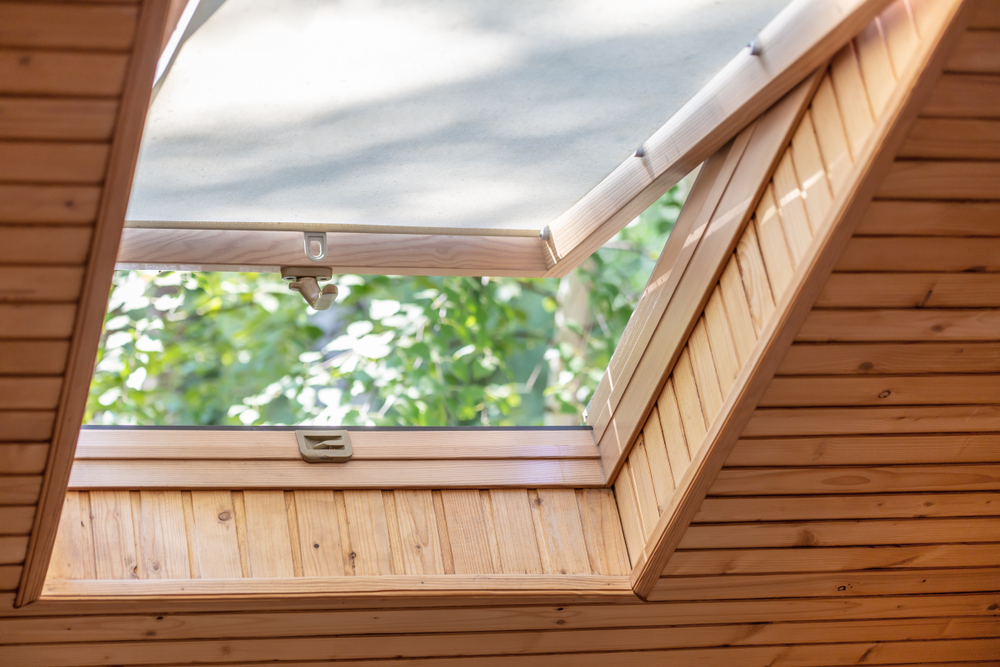 Opened roof window with blinds or curtain in wooden house attic