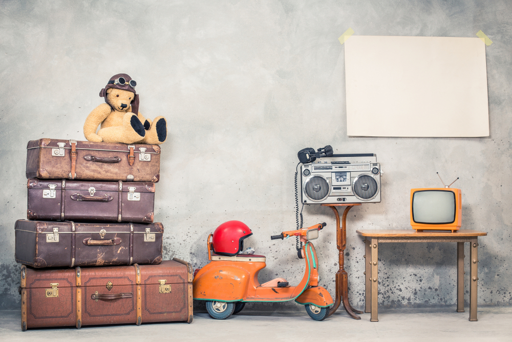 Retro Teddy Bear toy in aviator's hat, aged travel valises, children's pedal scooter, helmet, cassette boombox with headphones, TV, paper poster blank on concrete wall
