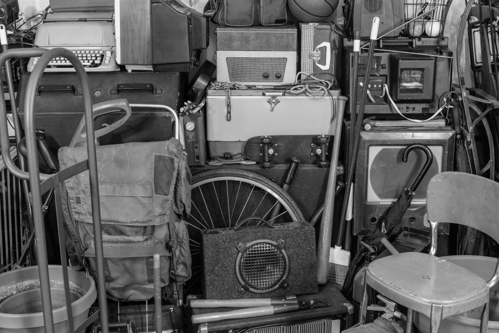 Vintage attic storage area with old tools, gardening, music and sports equipment in black and white.
