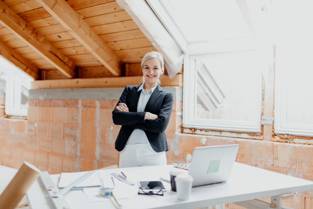 young, pretty, blonde architect standing in the attic